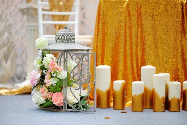 Klatka z kwiatami i świeczkami jako dekoracja na przyjęciu weselnym