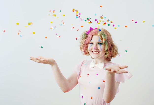 Klaun dziewczyna wieje konfetti z rąk