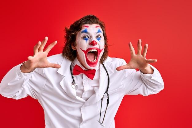 Klaun odstraszający mężczyzna krzyczy na aparat z rozpostartymi ramionami. noszenie kombinezonu medycznego. pantomima, usługi medyczne, pojęcie opieki zdrowotnej