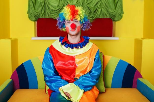 Klaun siedzi na kolorowej kanapie.