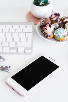 Klawiatura blisko smartphone i ciastek na talerzu