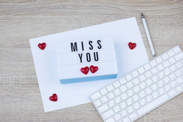 Klawiatura, długopis i lightbox ze słowami miss you