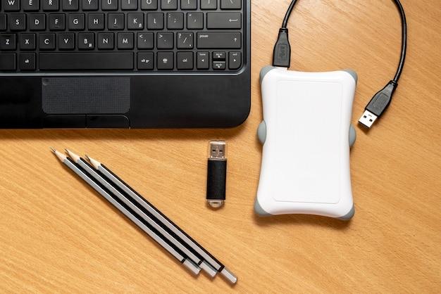 Klawiatura do laptopa. ołówki, pendrive i zewnętrzny dysk twardy na drewnianym stole, widok z góry. pojęcie biura domowego i pracy zdalnej