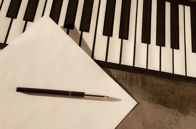 Klawiatura fortepianowa, długopis i czysty papier. pojęcie komponowania muzyki, piosenek, kreatywności, uczenia się.