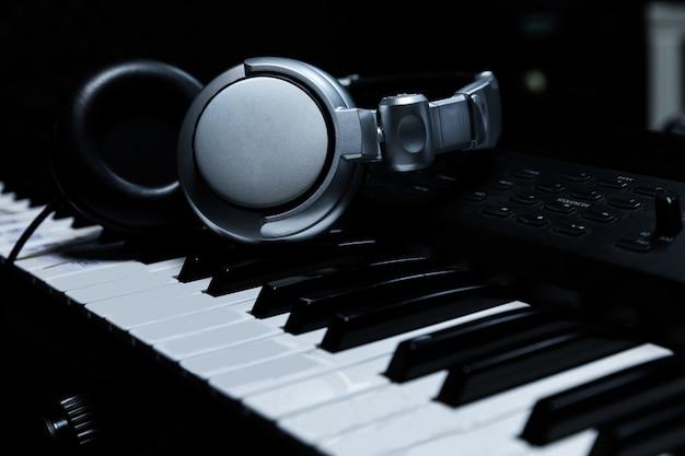 Klawiatura fortepianowa ze słuchawkami do muzyki, słuchawki na klawiaturze fortepianu, zbliżenie, słuchawki na tle pianina elektrycznego na tle instrumentów muzycznych.