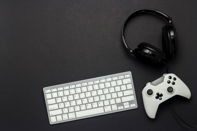 Klawiatura, gamepad i słuchawki na czarnym tle. koncepcja gry na konsoli, gry. leżał płasko, widok z góry.