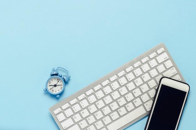 Klawiatura i biały telefon komórkowy, budzik na niebieskim tle. koncepcja biznesowa, praca biurowa, aplikacja mobilna i strona internetowa. leżał płasko, widok z góry