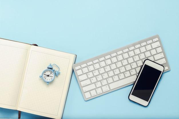 Klawiatura i biały telefon komórkowy, budzik, pamiętnik na niebieskim tle. koncepcja biznesowa, praca biurowa, aplikacja mobilna i strona internetowa. leżał płasko, widok z góry.