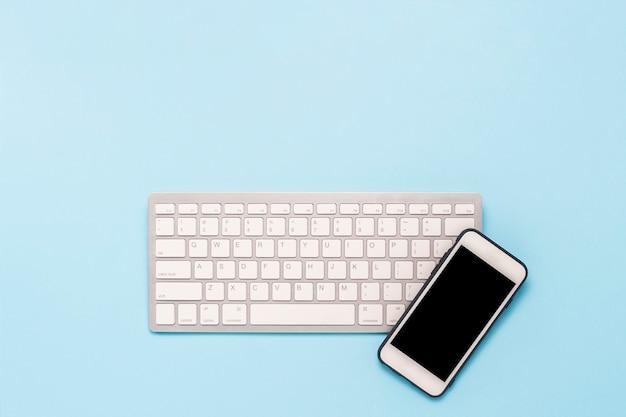 Klawiatura i biały telefon komórkowy na niebieskim tle. koncepcja biznesowa, praca biurowa, aplikacja mobilna i strona internetowa. leżał płasko, widok z góry.