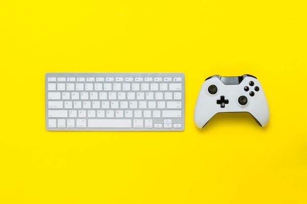 Klawiatura i joystick na żółtym tle. gra koncepcyjna, konsola. leżał płasko, widok z góry