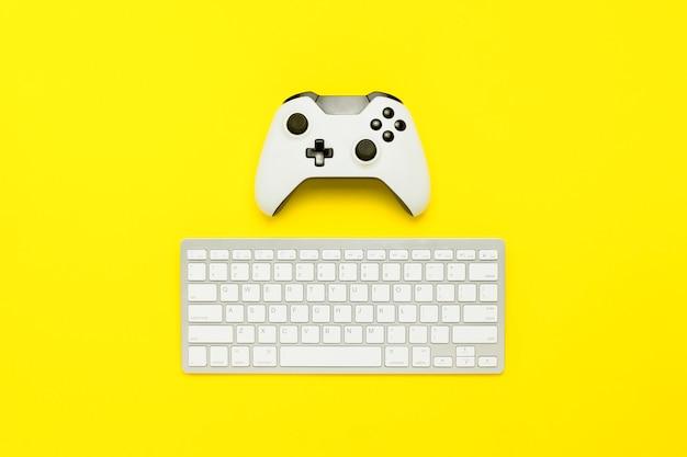 Klawiatura i kontroler na żółtym tle. gra koncepcyjna, konsola. leżał płasko, widok z góry