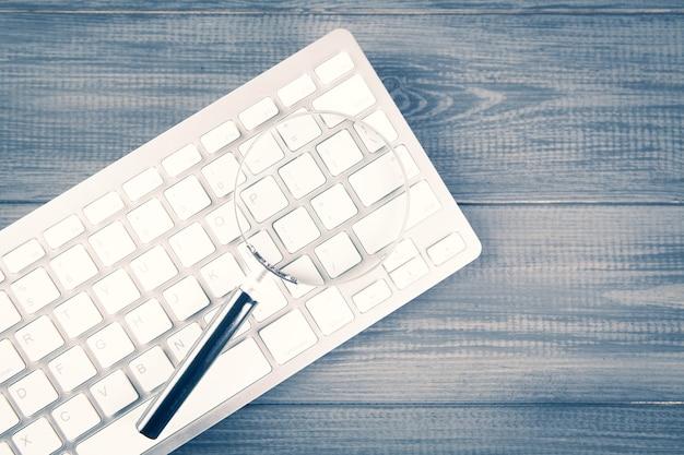 Klawiatura i lupa. koncepcja wyszukiwania na szarym drewnianym stole