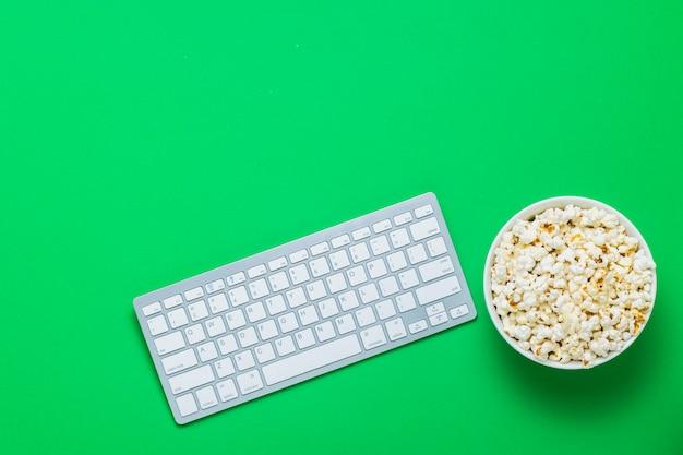 Klawiatura i miska z popcornem na zielonym tle. koncepcja oglądania filmów, programów telewizyjnych, programów, sportu online. leżał płasko, widok z góry