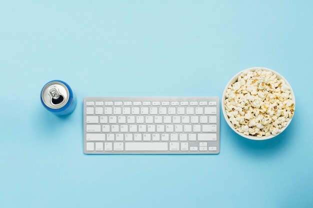Klawiatura i puszka z napojem, napojem energetycznym, miską popcornu na niebieskim tle. koncepcja oglądania filmów, programów telewizyjnych, wydarzeń sportowych online. leżał płasko, widok z góry