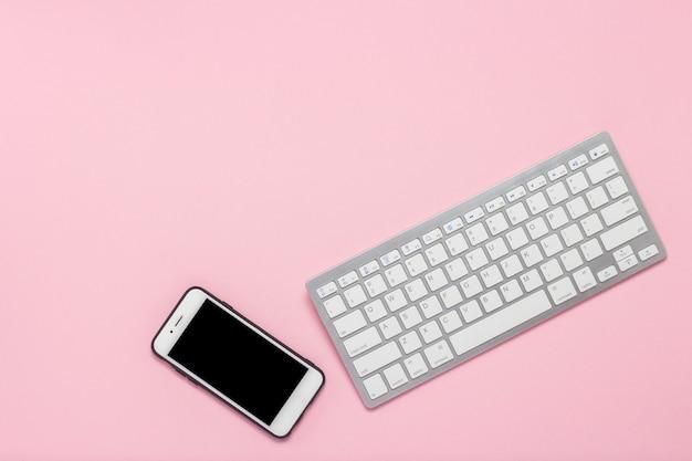 Klawiatura i telefon komórkowy na różowym tle. pomysł na biznes. leżał płasko, widok z góry.