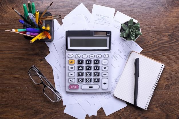 Klawiatura kalkulatora z czekami ze sklepu na drewnianej podłodze