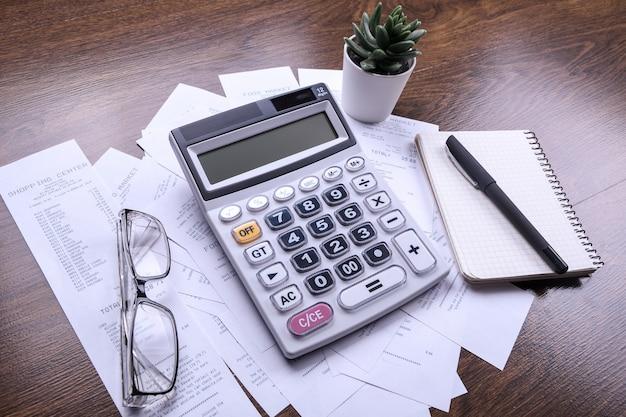 Klawiatura kalkulatora z czekami ze sklepu z zakupów na drewnianej podłodze. widok z góry. skopiuj miejsce