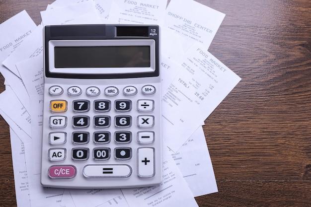 Klawiatura kalkulatora z czekami ze sklepu z zakupów na tle drewnianej podłogi. widok z góry. skopiuj miejsce