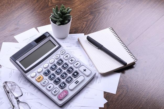 Klawiatura kalkulatora z czekami ze sklepu z zakupów na tle drewnianej podłogi