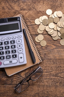 Klawiatura kalkulatora, złote monety, długopis i notatnik na drewnianym stole podłogowym. widok z góry. skopiuj miejsce
