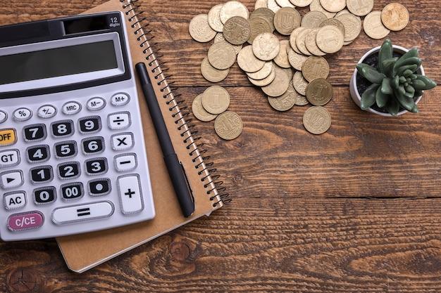 Klawiatura kalkulatora, złote monety, długopis i notatnik na tle drewnianej podłogi. widok z góry. skopiuj miejsce.