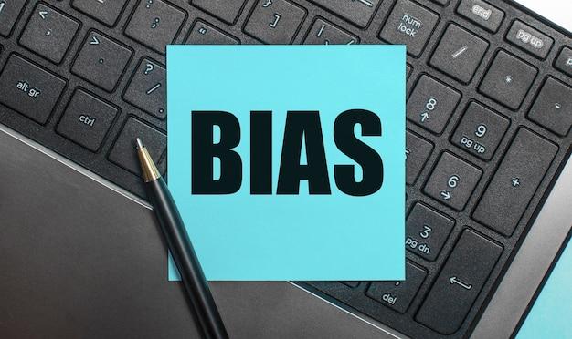 Klawiatura komputera posiada długopis i niebieską naklejkę z napisem bias. leżał płasko.
