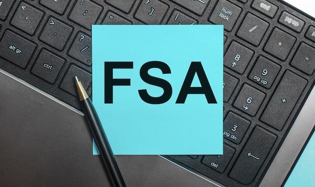 Klawiatura komputera posiada długopis i niebieską naklejkę z napisem fsa flexible spending account. leżał płasko.