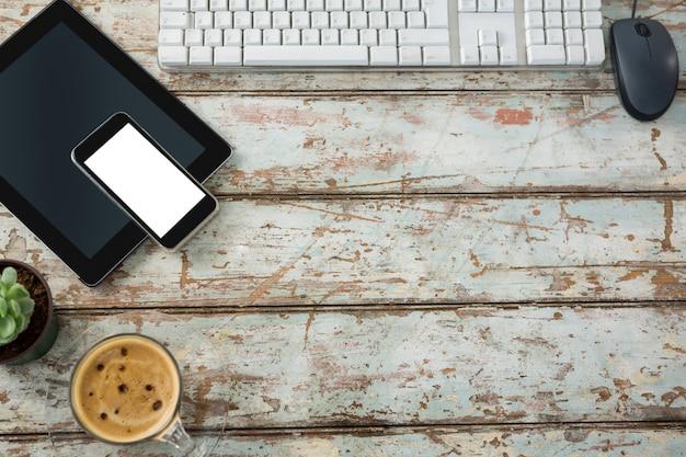 Klawiatura komputerowa, mysz, cyfrowy tablet i smartfon z filiżanką kawy