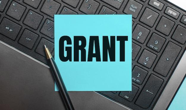 Klawiatura komputerowa posiada długopis i niebieską naklejkę z napisem grant. leżał płasko.