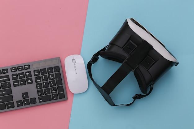 Klawiatura komputerowa z kaskiem vr na różowym niebieskim pastelu. nowoczesne gadżety