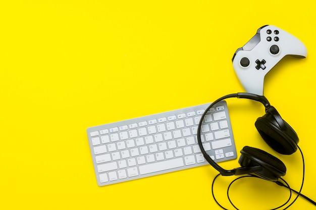 Klawiatura, kontroler i słuchawki na żółtym tle. koncepcja konsoli do gier. leżał płasko, widok z góry