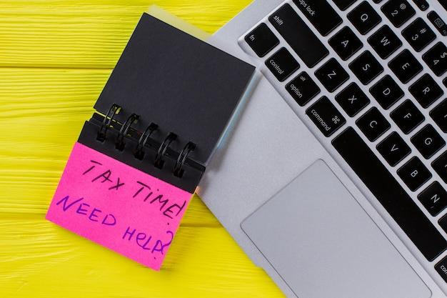 Klawiatura laptopa i przypomnienie o podatku. żółte drewniane tło. widok z góry na płasko.