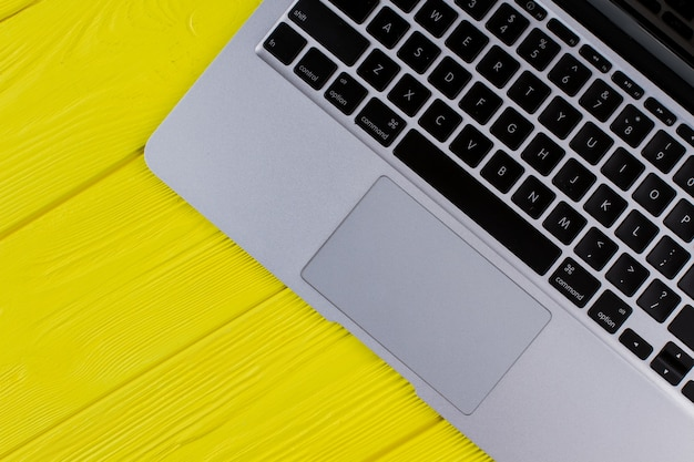 Klawiatura laptopa z widokiem z góry. żółte drewniane tło.