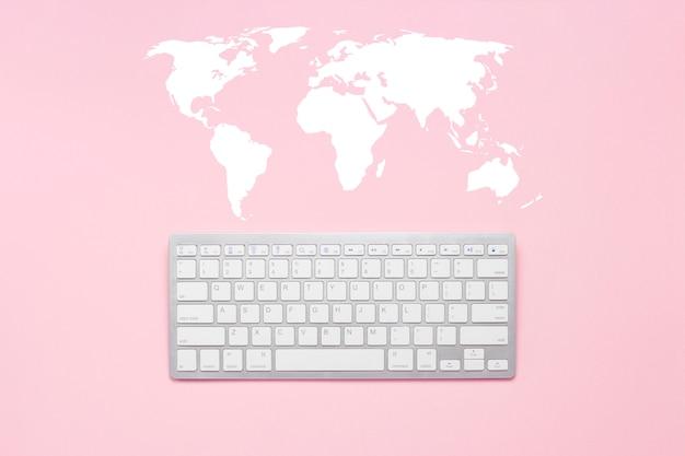 Klawiatura na różowym tle. mapa świata. koncepcja globalnej sieci, komunikacja ze światem, w dowolnym miejscu na świecie. leżał płasko, widok z góry.