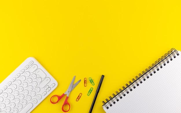 Klawiatura nożyczki felttip notebook na żółtym tle kopii przestrzeni