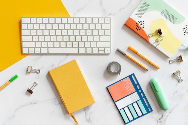 Klawiatura otoczona kolorowymi artykułami biurowymi