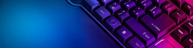 Klawiatura profesjonalnych graczy wideo z komputerem. cybersportowe mistrzostwa, neonowe niebieskie światła