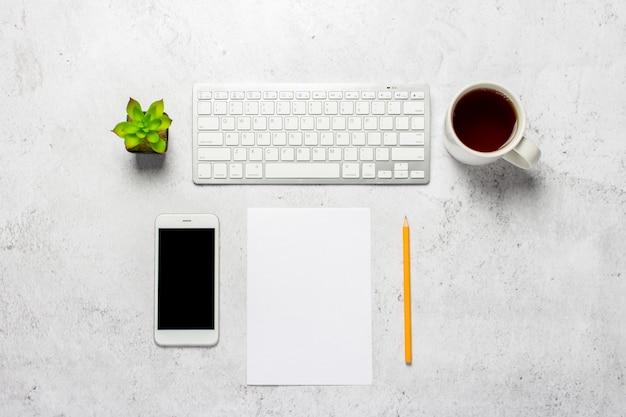 Klawiatura, pusty arkusz papieru i ołówek, telefon, filiżanka kawy i roślina doniczkowa na betonowym tle.