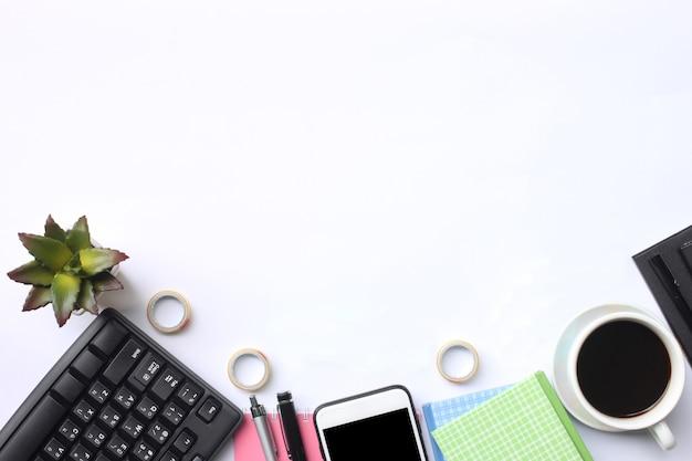 Klawiatura, smartfon, notatnik, filiżanka kawy, długopis i materiały na białym biurku.