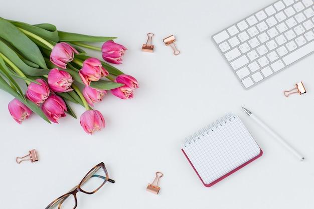 Klawiatura, spinacze, okulary, notatnik, długopis i bukiet różowych tulipanów