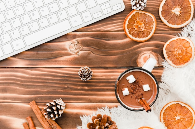 Klawiatura w pobliżu gorącej czekolady, pomarańczy i guzków drzewa