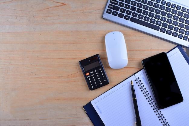 Klawiatura z myszką, wieczne pióro, notatnik, kalkulator i smartfon na stole