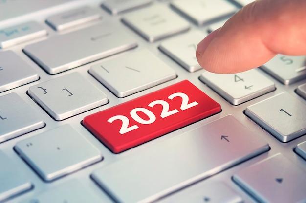 Klawiatura z napisem happy 2022 i palcem wciskającym klawisz enter. kolorowy przycisk na szaro-srebrnej klawiaturze nowoczesnego ultrabooka. napis na przycisku