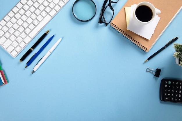 Klawiatura z notatnikiem i kawą stacjonarną na stole