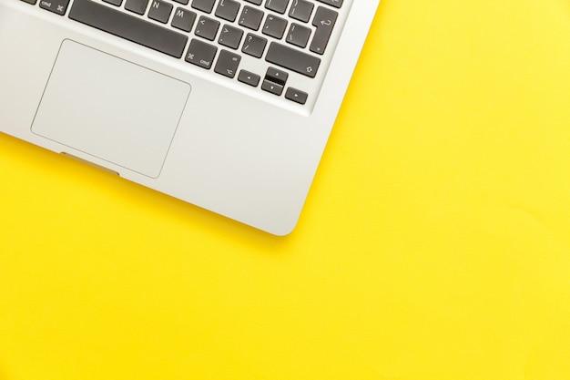 Klawiaturowy laptop odizolowywający na żółtym biurka tle.