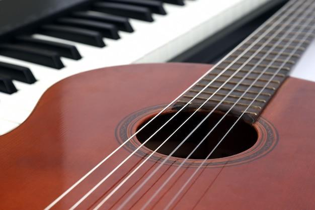 Klawisze fortepianu i gitara klasyczna z bliska na białym tle