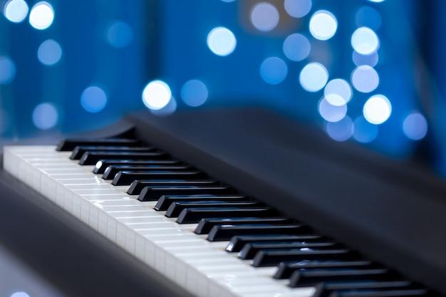 Klawisze fortepianu na niebieskim bokeh