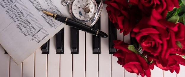 Klawisze fortepianu, nuty, wieczne pióro, zabytkowy zegar i bukiet róż