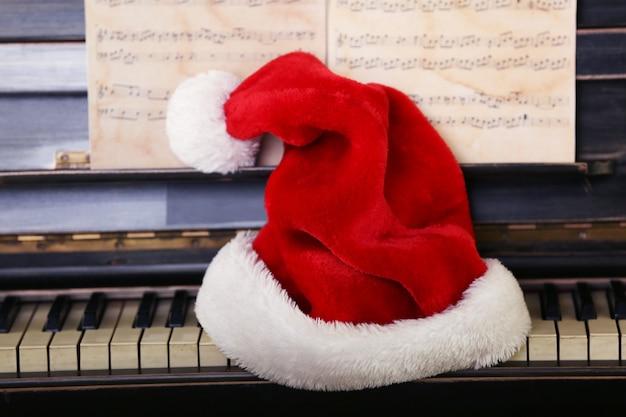 Klawisze fortepianu ozdobione czapką świętego mikołaja, zbliżenie