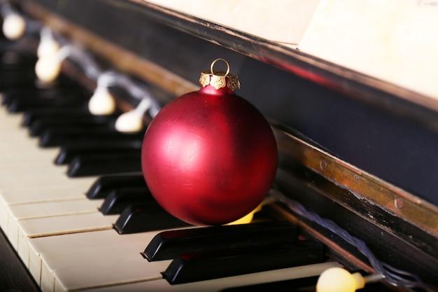 Klawisze fortepianu ozdobione dekoracyjnymi światłami i czerwoną kulką, z bliska